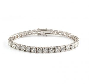 An 18K white gold diamond tennis bracelet featuring 33 claw set round brilliant cut diamonds in four claw baskets and a diamond set clasp. Each diamond is GIA certified.