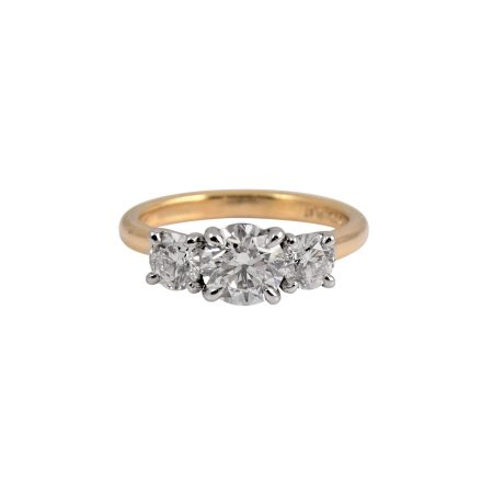 This round brilliant cut trilogy two tone engagement ring is set in platinum and 18K yellow gold . Featuring three round brilliant cut diamonds, the center diamond is 0.90ct and the two either side are 0.30ct each. They are each set into a four claw setting which is attached to a half round band. Carat: 1 = 0.90ct, 2 = 0.60ct Colour: F Clarity: VS2