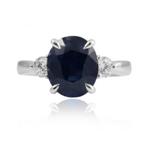 18K white gold, oval blue sapphire ring with diamonds, is centrally set with a 4.07ct oval blue sapphire in a four claw setting. With a round brilliant diamond on either side.