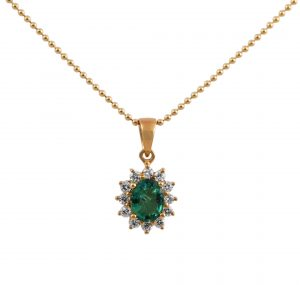 An 18K Emerald and diamond halo pendant set in yellow gold. Featuring a 0.49ct oval Emerald set in a four claw setting, surrounded by a halo of round brilliant cut diamonds in a claw setting.