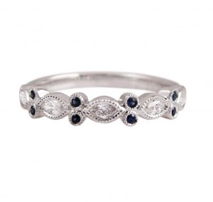 An 18K white gold marquise diamonds and round sapphires band. Made up of marquise shapes in a row, each section is bead set with diamonds and finished off with a mil grain edge with two small :round cut blue sapphires.