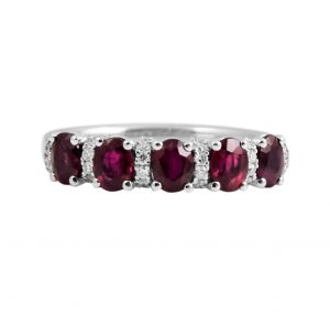 An 18K white gold oval Rubies and diamond band ring. Set with five oval Rubies and thirty six round brilliant cut diamonds all in a fine claw setting spread across the top of the band.