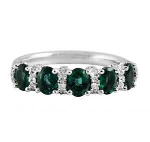 An 18K white gold oval Emeralds and diamond band ring. Set with five oval Emeralds and thirty six round brilliant cut diamonds all in a fine claw setting spread across the top of the band.