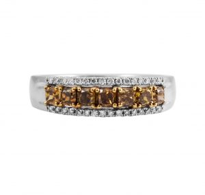 An 18K 2-tone natural colour diamond ring band . The ring features a 0.72ct round yellow, orange brown diamond set in a four claw yellow gold setting with small round brilliant cut diamonds on either side set on the top of the band being all in white gold.