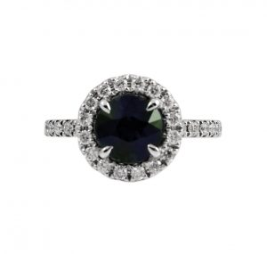 An 18K white gold Australian aqua green sapphire and diamond ring. Featuring a 1.81ct round Australian green sapphire surrounded by a fine halo of round brilliant cut diamonds and down the shoulders of the ring.