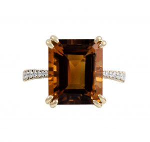 A 9K yellow gold Citrine and diamond cocktail dress ring. Featuring a 5.9ct Citrine step cut in a double claw set with diamonds going half way around the band. Gemstone Carat Citrine: 5.99ct Diamond: 16 = 0.20ct RING SIZE: M