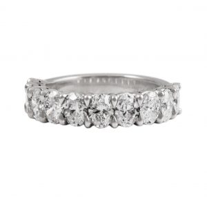 A Platinum Eternity Ring with oval diamonds claw set in a unique styled design. The band is set with 10 oval brilliant cut diamonds. This design can be made with any size diamonds as a custom make, to suit. Diamond carat: 10 = 2.41ct F VS RING SIZE: L