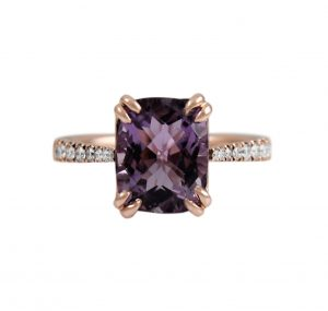 A 9K rose gold Amethyst and diamond dress ring. Set with a 2.94ct cushion cut Amethyst claw set with diamonds half way around the band. Gemstone Carat: Amethyst = 2.94ct Diamond Carat: 26 = 0.21ct RING SIZE: M