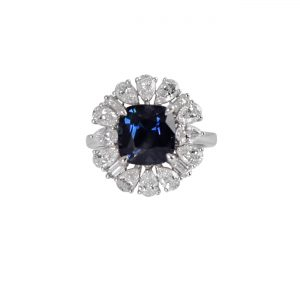 This 18K white gold, blue sapphire cushion cut ring with diamonds, is centrally set with a GIA certified 4.05ct Australian natural blue sapphire in a four claw setting. With pear cut and baguettes diamonds all around it making it a spectacular and unique designed ring. GEMSTONE CARAT: Australian Blue Sapphire : 4.05ct Diamonds : 16 = 1.86ct RING SIZE: M1/2