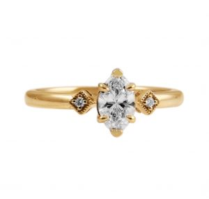 Marquise diamond ring set in 18K Yellow Gold. Featuring a 0.50ct Marquise diamond set with six claws, with two little diamond shapes with a mill grain finish set with a small round brilliant cut diamond on each side of the Marquise center stone. CARAT  : 0.50ct MARQUISE COLOUR : H CLARITY : VS2