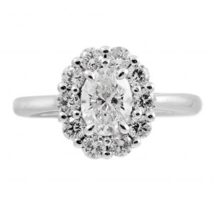 An 18K white gold oval halo diamond ring. Featuring a 0.70ct oval brilliant cut diamond surrounded by a halo of 10 round brilliant cut diamonds. CARAT  : 1 = 0.70ct, 10 = 0.603ct COLOUR : G CLARITY : VVS2 Size M
