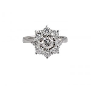 An 18K white gold diamond flower engagement - dress ring. The ring is set with a 0.43ct round brilliant cut diamond in the center which is set in a fine 8 claw setting. Which is then surrounded by 8 smaller round brilliant cut diamonds in a flower shape basket setting attached to a tapered band. Carat: 1 Centre Diamond = 0.43ct, G SI2 D8 = 1.23ct F VS2 Ring Size: L1/2